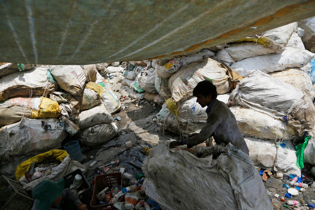 ". A rag picker opens a sack of plastic waste to segregate for recycling on the eve of World Environment day at a junkyard in Kathmandu, Nepal, Monday, June 4, 2018. The theme for this year\'s World Environment Day, marked on June 5, is ""Beat Plastic Pollution.\"" (AP Photo/Niranjan Shrestha)"