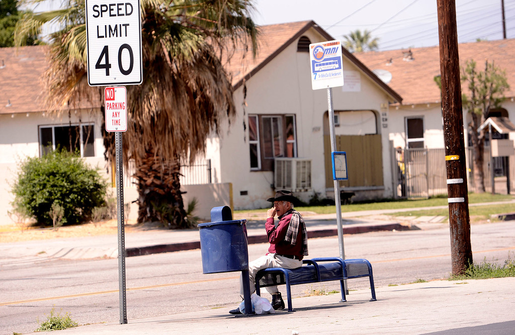 . A man waits at a bus stop  at the corner of North Sierra Way and Baseline Street in San Bernardino April 22, 2013.   GABRIEL LUIS ACOSTA/STAFF PHOTOGRAPHER.