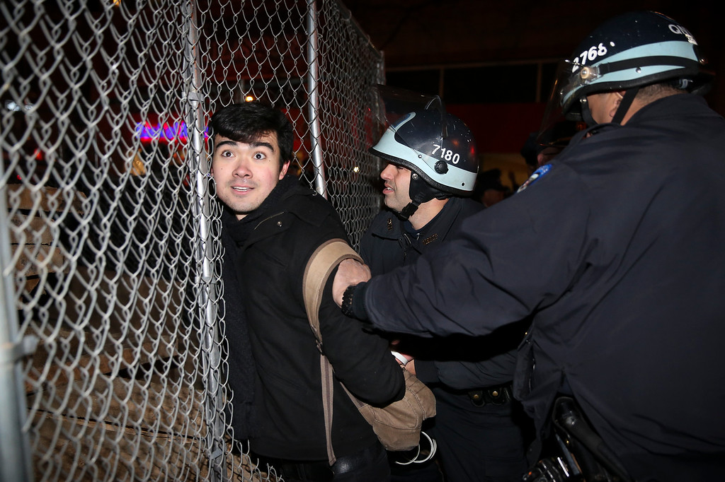 . Protestor Michael Alvarez is arrested during a march against a grand jury\'s decision not to indict the police officer involved in the death of Eric Garner, Friday, Dec. 5, 2014, in New York. A grand jury cleared a white New York City police officer Wednesday in the videotaped chokehold death of Garner, an unarmed black man, who had been stopped on suspicion of selling loose, untaxed cigarettes, a lawyer for the victim\'s family said. (AP Photo/John Minchillo)