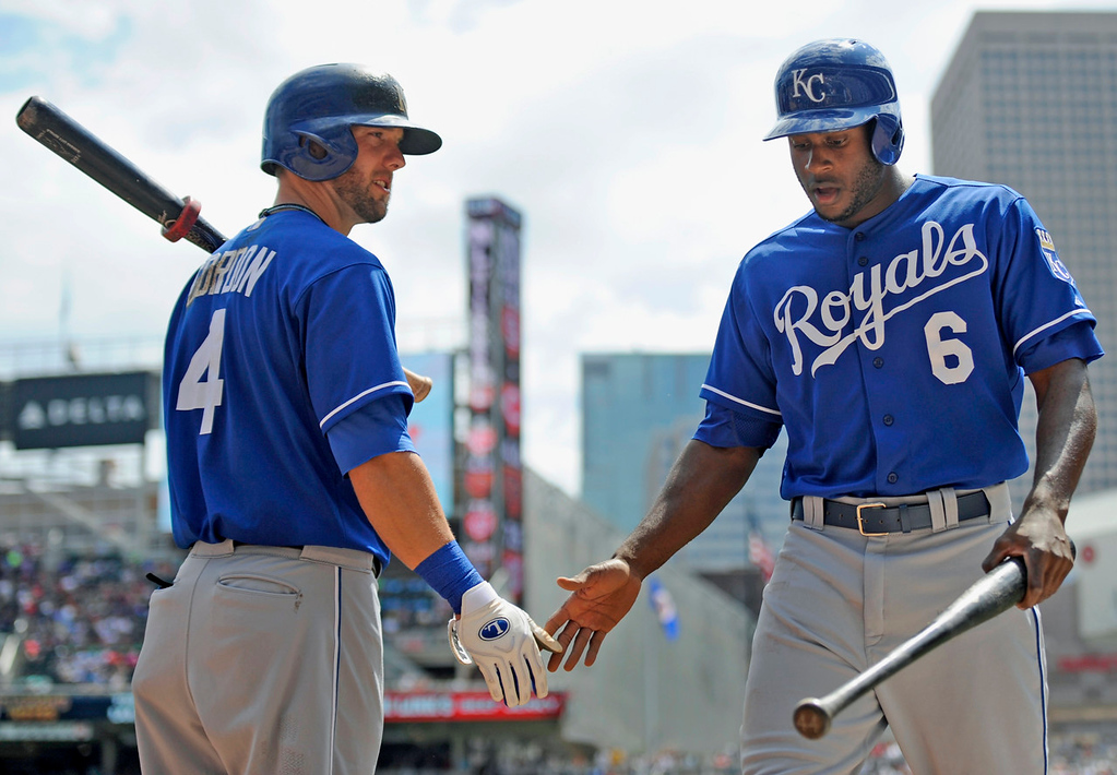 . Kansas City\'s Alex Gordon, left, congratulates teammate Lorenzo Cain, who scored on a single by Justin Maxwell against the Twins during the second inning. (Photo by Hannah Foslien/Getty Images)