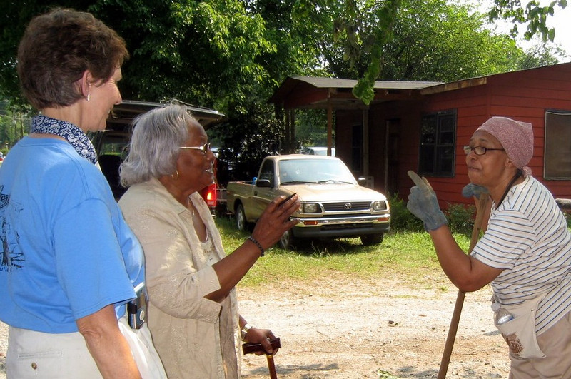 Homeowner Lillie Miller (right) enjoys visiting with one of her friends from the neighborhood, Fannie Crawford, as Linda Fuller stands near.  ky