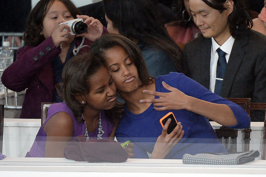 . Sasha (L) and Malia Obama, daughters of U.S. President Barack Obama, take a photo of themselves during the Presidential Inaugural Parade on January 21, 2013 in Washington, DC.   JOE KLAMAR/AFP/Getty Images