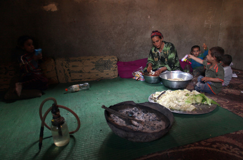 . A Palestinian refugee prepares food as her children sit next to her in their house in Gezirat al-Fadel village, Sharqiya, about 150 kilometers  (93 miles) east of Cairo, Egypt.  (AP Photo/Khalil Hamra)