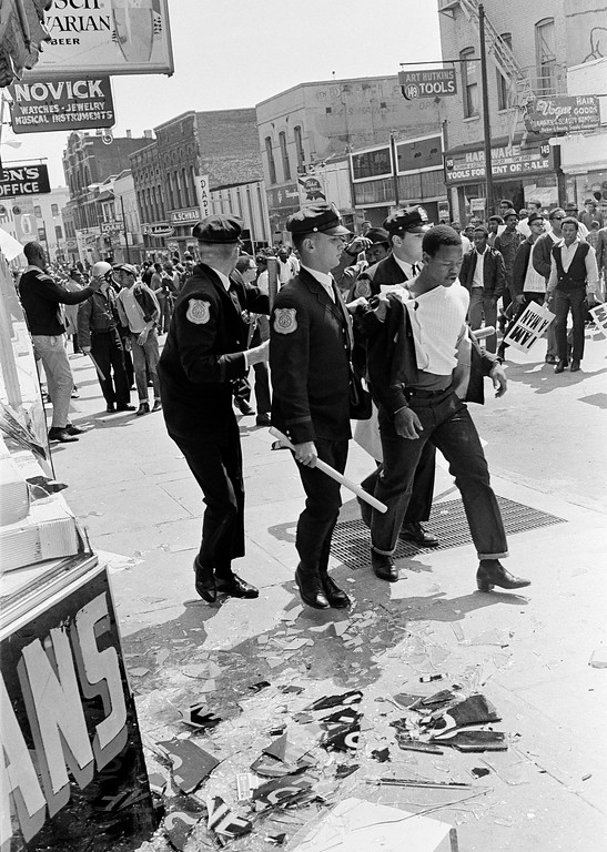 . Two policemen take a looting suspect into custody on the glass littered sidewalk of downtown Memphis, Tenn., as a third policeman peers over his shoulder at some 6,000 demonstrators in the street,  March 28, 1968. Racial tension remained high in the city after violence erupted midway through a march led by Dr. Martin Luther King Jr., in support of striking garbage workers. (AP Photo/Jack Thornell)