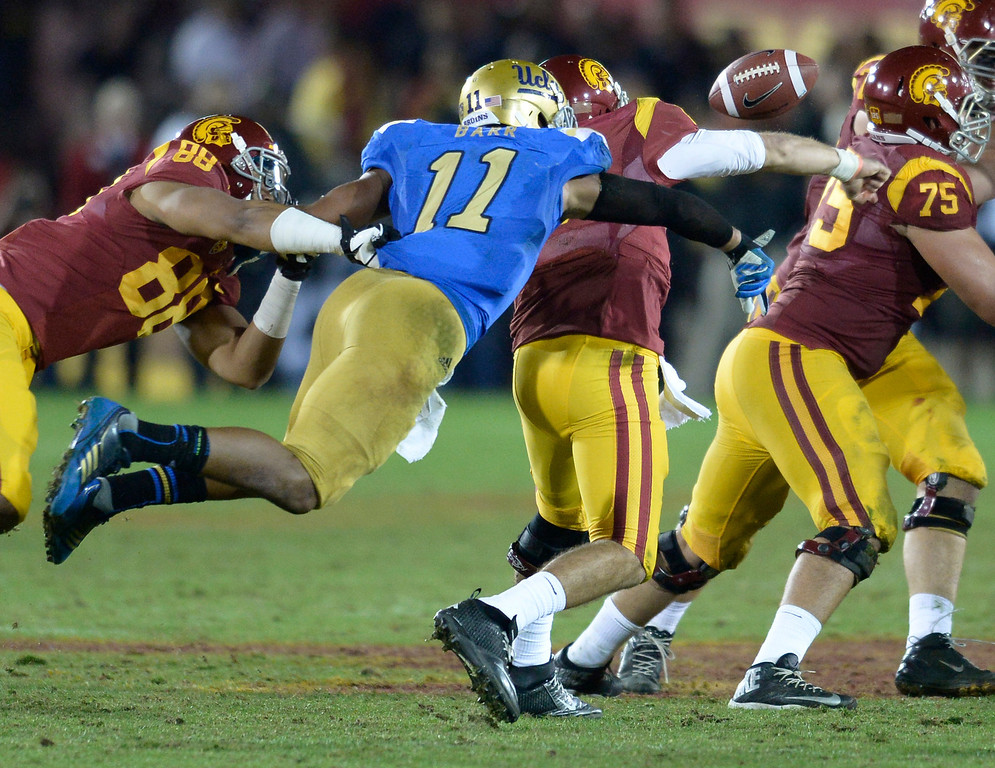 . UCLA #11Anthony Barr strips the ball from USC QB Cody Kessler in the 4th quarter. UCLA defeated USC 35 to 14 in a matchup of cross town rivals at the Los Angeles Memorial Coliseum in Los Angeles, CA.  photo by (John McCoy/Los Angeles Daily News)