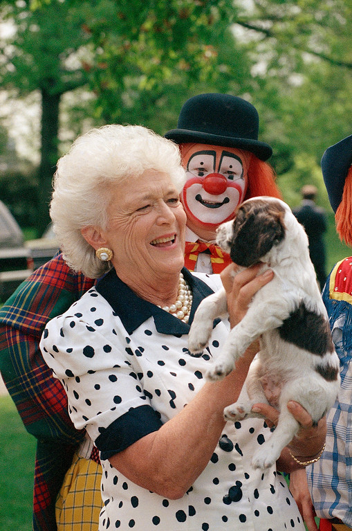 . First lady Barbara Bush holds one of the first family puppies, as a circus clown looks on in Washington on the South Lawn of the White House, April 27, 1989, after a performance by some members of the circus at a Reading Is Fundamental outing hosted by Mrs. Bush. (AP Photo/J. Scott Applewhite)