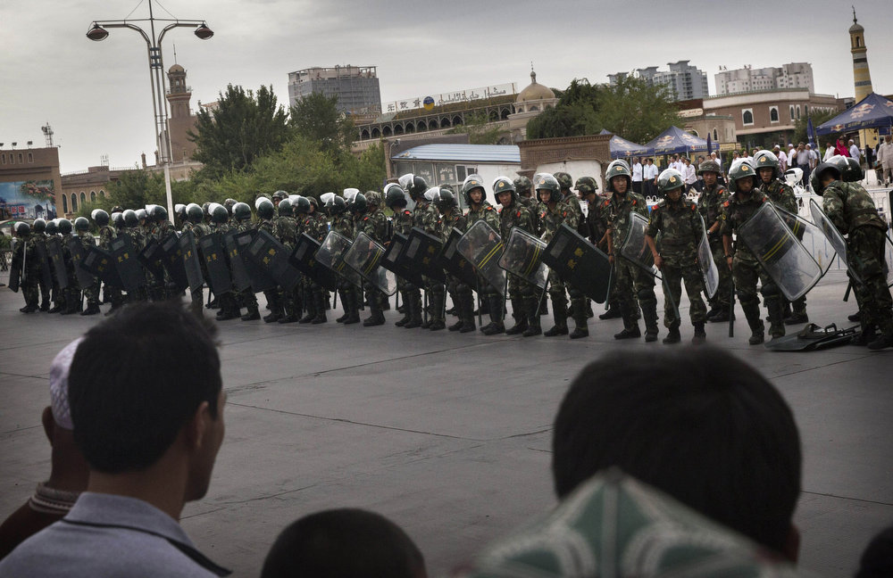 . KASHGAR, CHINA - JULY 30:  Chinese soldiers in riot gear secure the area outside the Id Kah Mosque, after Imam Jumwe Tahir was killed by assailants following early morning prayers on July 30, 2014 in old Kashgar, Xinjiang Province, China. Nearly 100 people have been killed in unrest in the restive Xinjiang Province in the last week in what authorities say is terrorism but advocacy groups claim is a result of a government crackdown to silence opposition to its policies. China\'s Muslim Uyghur ethnic group faces cultural and religious restrictions by the Chinese government. Beijing says it is investing heavily in the Xinjiang region but Uyghurs are increasingly dissatisfied with the influx of Han Chinese and uneven economic development.  (Photo by Getty Images)