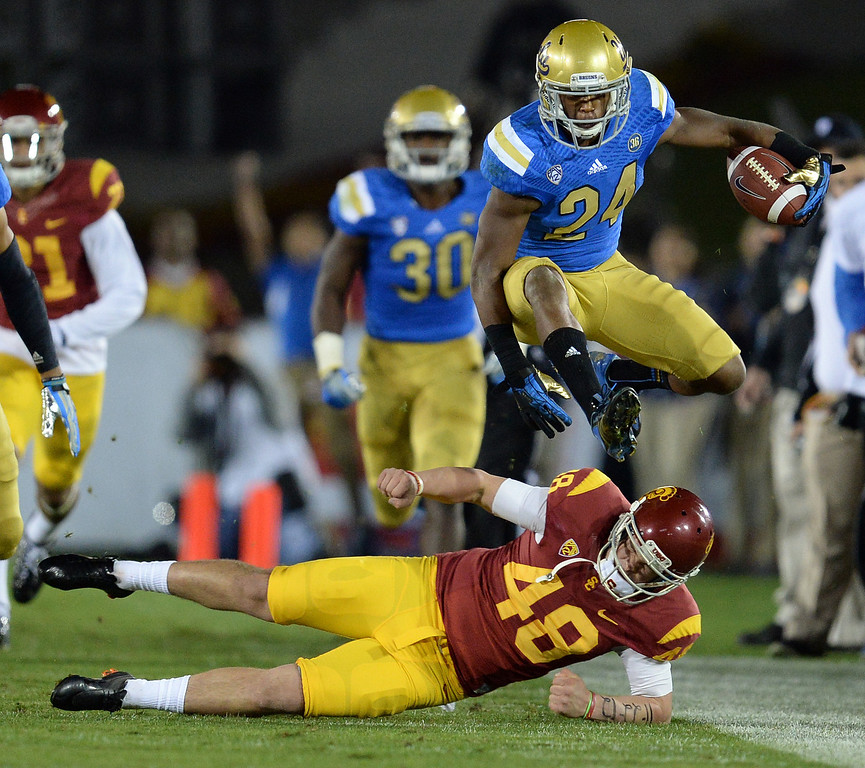 . UCLA\'s Ishmael Adams #24 hurdles USC�s Andre Heidari #48 while returning a kick off for a big gain during their game at the Los Angeles Memorial Coliseum Saturday, November 30, 2013.  (Photo by Hans Gutknecht/Los Angeles Daily News)