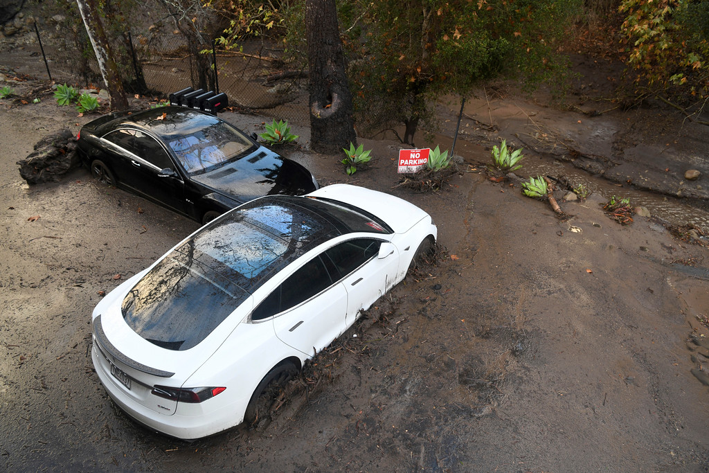. Cars sit in mud at a housing complex in Montecito, Calif., Tuesday, Jan. 9, 2018. (AP Photo/Michael Owen Baker)