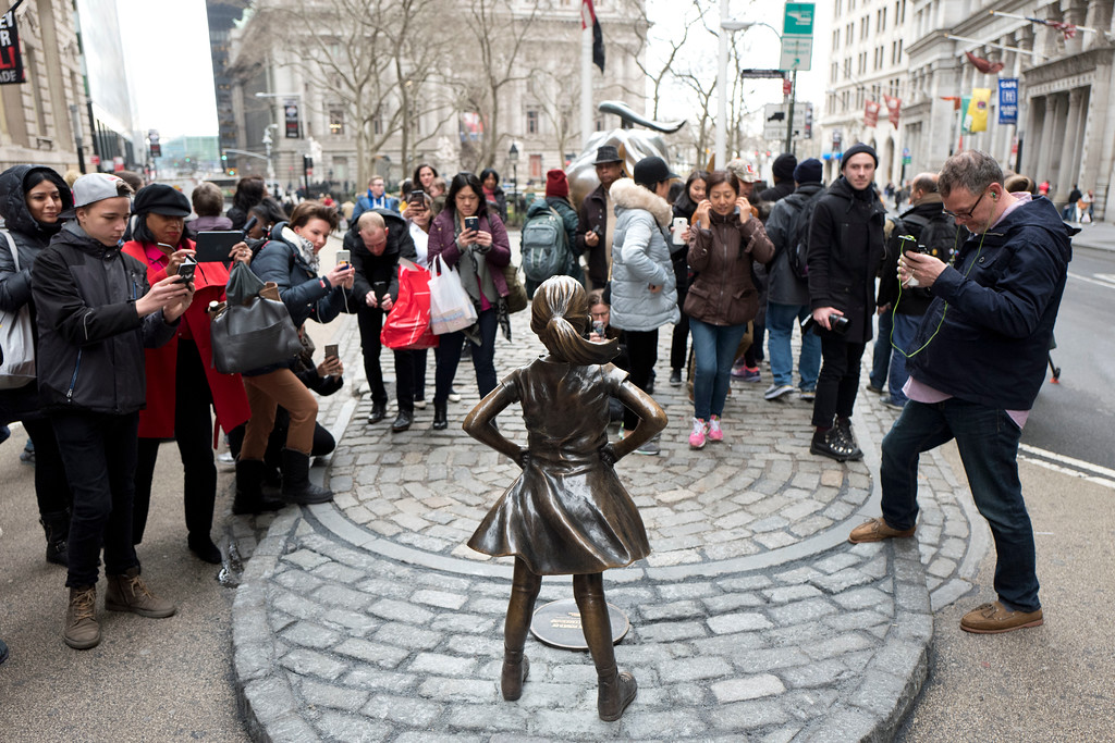 ". A crowd gathers around a statue of a fearless girl, Wednesday, March 8, 2017, in New York. The statue was installed by an investment firm in honor of International Women\'s Day. An inscription at the base reads, ""Know the power of women in leadership. She makes a difference. State Street Global Advisors.\"" (AP Photo/Mark Lennihan)"