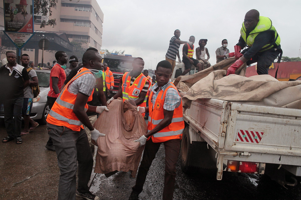 . Rescue workers carry the remains, of a person onto the back of a truck after being killed in a gas station explosion  in Accra, Ghana, Thursday, June 4, 2015. Flooding in Ghana\'s capital swept stored fuel into a nearby fire, setting off a huge explosion at a gas station that killed dozens of people and set alight neighboring buildings, authorities said Thursday. (AP Photo/Christian Thompson)