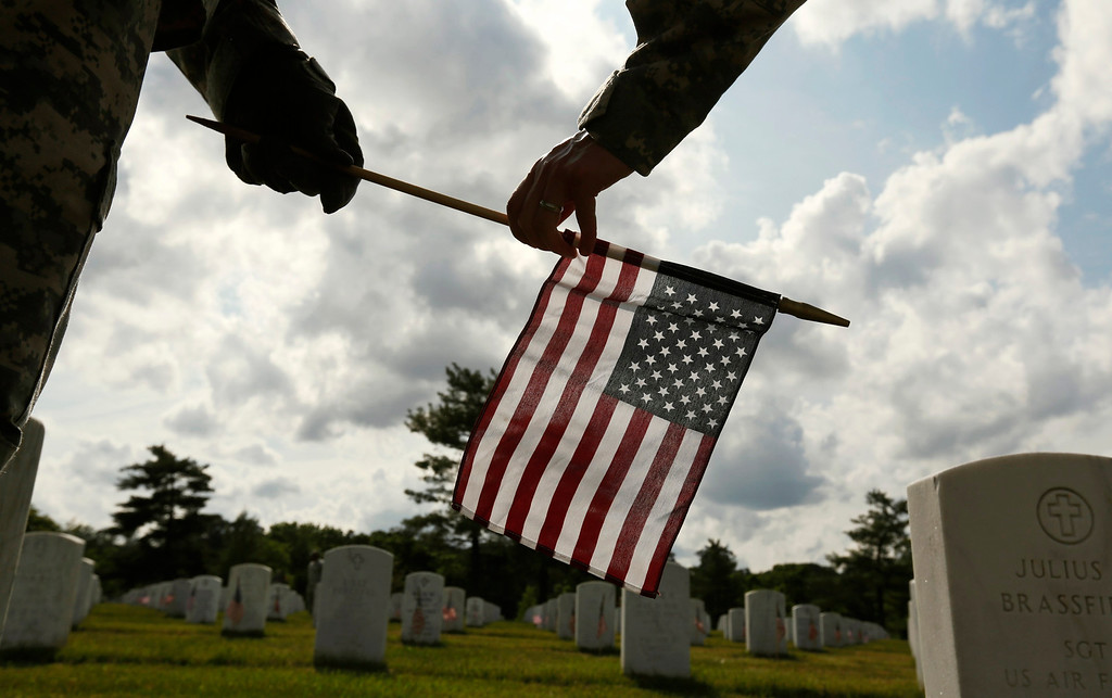 """. Soldiers from the Third U.S. Infantry Regiment (The Old Guard) place a flag at a grave at Arlington National Cemetery in Virginia May 23, 2013. The annual \""""Flags-In\"""" ceremony is held ahead of Memorial Day to honor the nation\'s fallen members of the military. Flags will be placed at more than 220,000 graves.    REUTERS/Kevin Lamarque"""