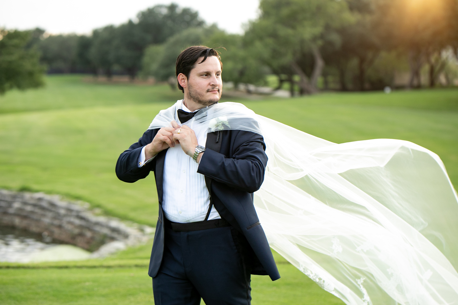 groom jokingly wearing the wedding veil as a cape