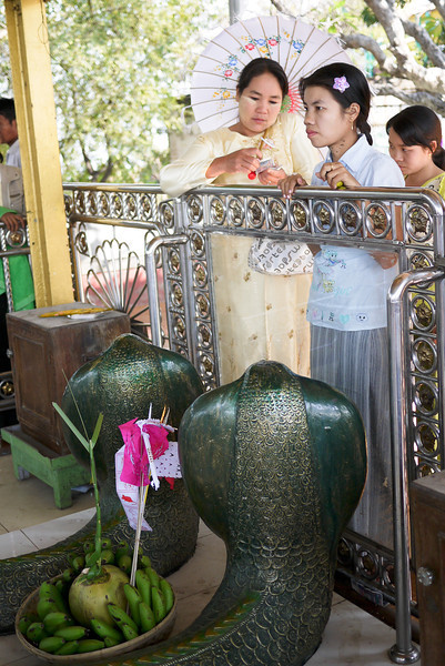 Women give offerings to the serpent Naga spirits on the top of Mandalay Hill, Burma.