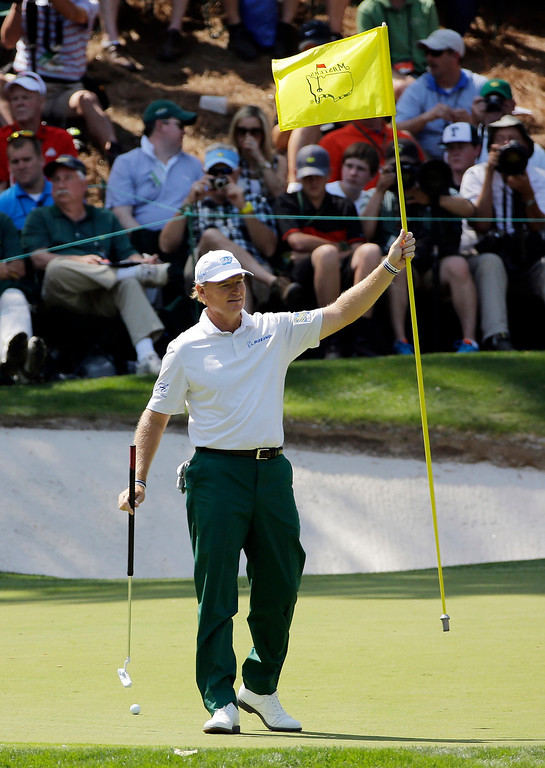 . Ernie Els, of South Africa, removes the pin on the ninth green during the par three competition at the Masters golf tournament Wednesday, April 9, 2014, in Augusta, Ga. (AP Photo/David J. Phillip)