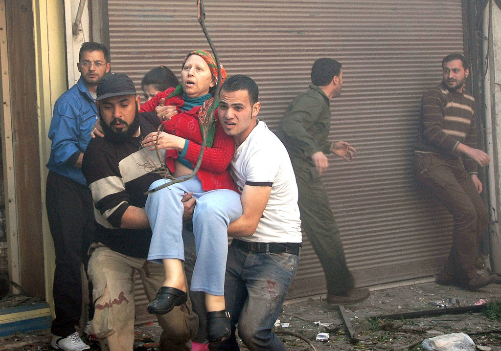 . A handout picture released by the official Syrian Arab News Agency (SANA) shows Syrians carrying a wounded woman following a car bomb explosion in al-Khudary Street in the Karm al-Loz neighbourhood of the central Syrian city of Homs on April 9, 2014. More than 150,000 people have been killed since the revolt began in March 2011 and nine million have been driven from their homes, including 2.6 million international refugees. (AFP PHOTO /HO/SANA)