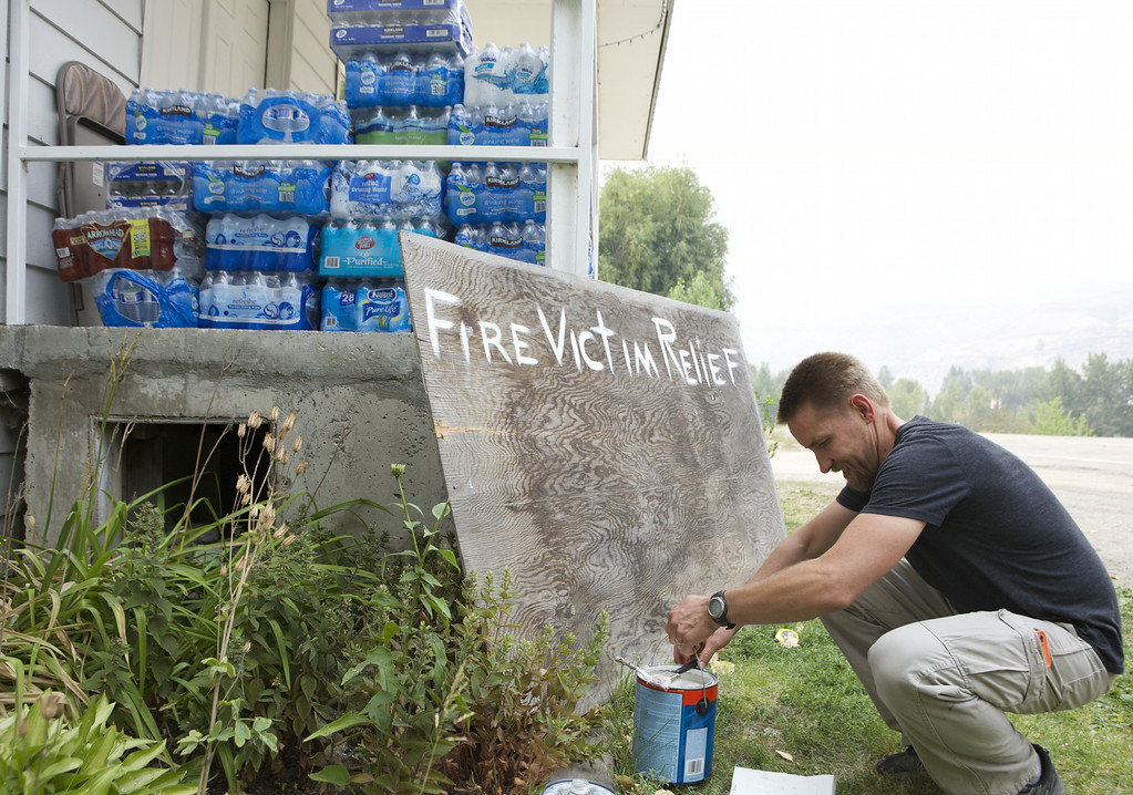 . Jason Getzin, the pastor at Calvary Chapel Fellowship paints a sign asking for donations for the fire victims on July 20, 2014 in Methow, Washington. Several fires throughout the state have destroyed hundreds of homes, forced evacuations and continue to threaten more local communities. (Photo by Stephen Brashear/Getty Images)