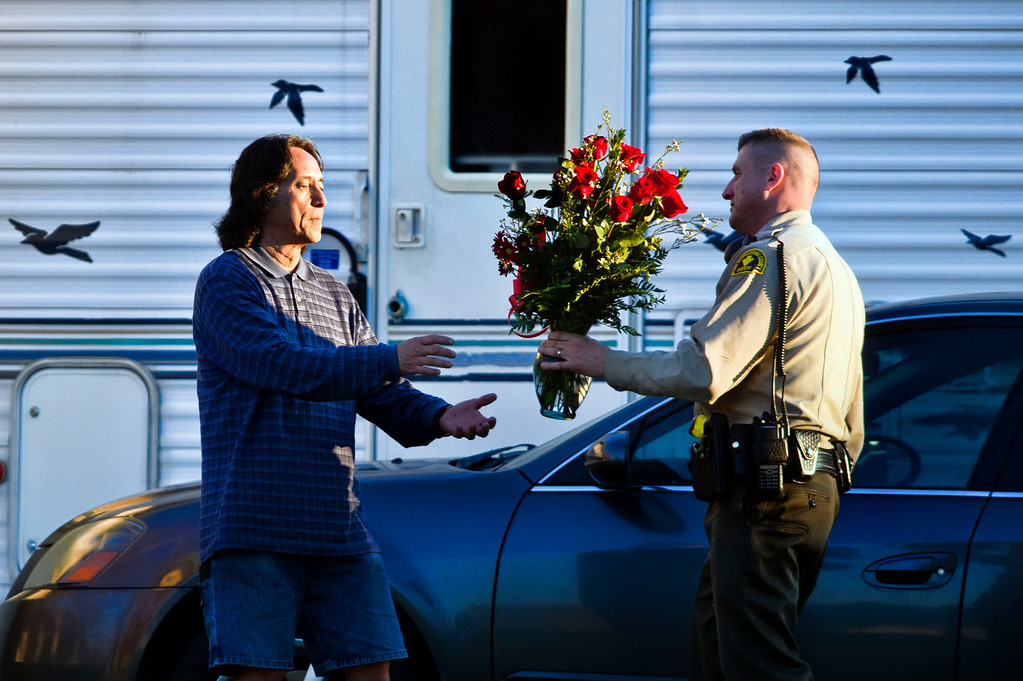 . A San Bernardino Sheriff\'s deputy brings flowers to a family member after it was delivered to the home of fallen Deputy Jeremiah MacKay in Redlands on Wednesday, Feb. 13, 2013. MacKay was killed during a shootout with ex-LAPD officer Christopher Dorner in Big Bear yesterday.  Watchara Phomicinda/Staff photographer