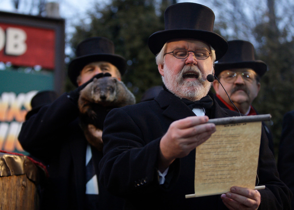 . Mike Johnston reads prognostication of the weather-predicting groundhog Punxsutawney Phil, who is being held by John Griffiths at left, at Gobbler\'s Knob on Groundhog Day, Monday, Feb. 2, 2009, in Punxsutawney, Pa. To the right is Butch Philliber.  The Groundhog Club said Phil saw his shadow and predicted six more weeks of winter. (AP Photo/Carolyn Kaster)