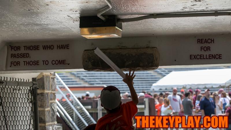 A fan gets lifted up to touch the Hokie Stone inside the Lane Stadium tunnel. (Mark Umansky/TheKeyPlay.com)