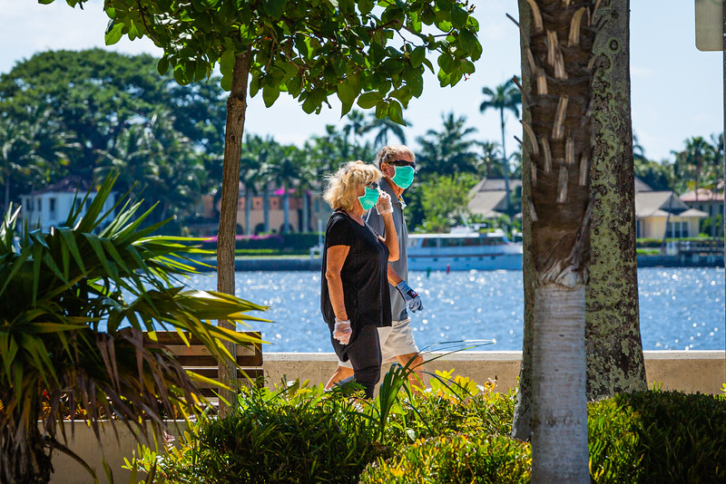 A couple walks along the waterfront in downtown West Palm Beach, Friday, May 1, 2020. [JOSEPH FORZANO/palmbeachpost.com]