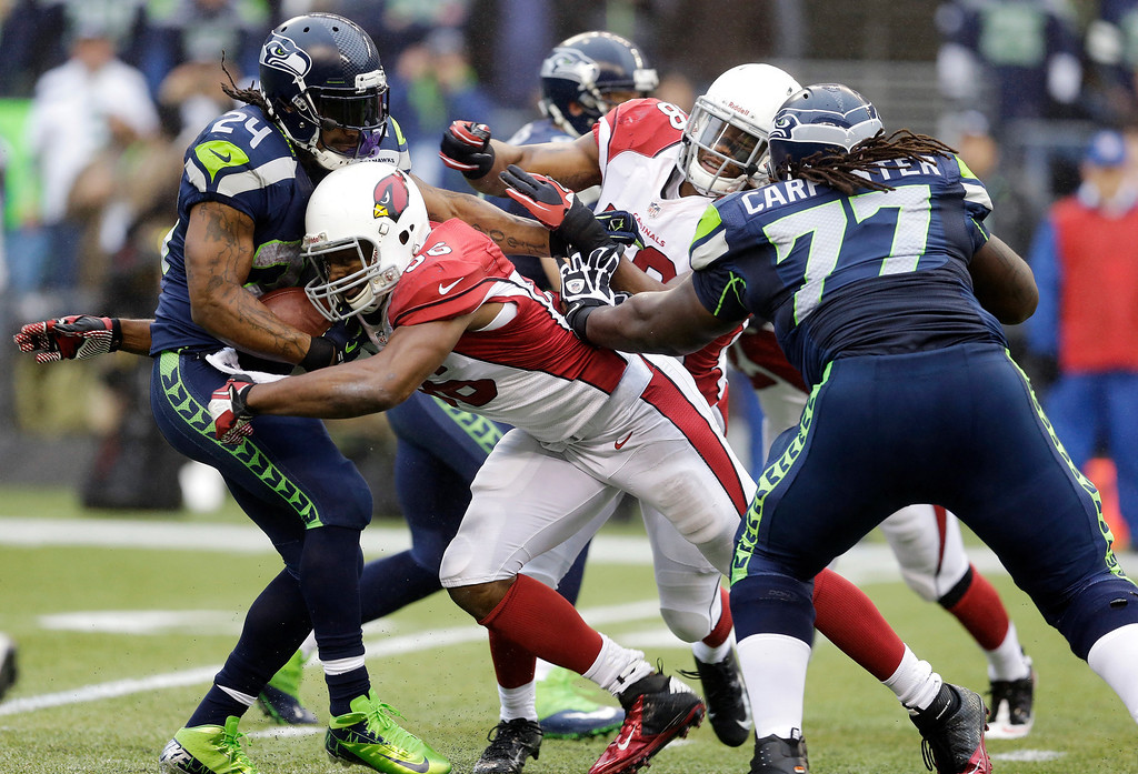 . Seattle Seahawks running back Marshawn Lynch, left, is tackled by Arizona Cardinals tight end Jake Ballard, center, as Seahawks\' James Carpenter (77) stands near, in the first half of an NFL football game, Sunday, Dec. 22, 2013, in Seattle. (AP Photo/Elaine Thompson)