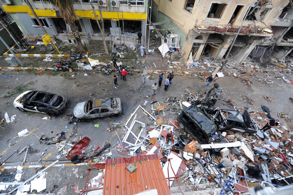 . People stand in a street strewn with debris on May 12, 2013 after a car bomb explosion went off on May 11 in Reyhanli in Hatay, just a few kilometers from the main border crossing into Syria. Turkey was reeling from twin car bomb attacks which left at least 43 people dead in a town near the Syrian border, with Ankara blaming pro-Damascus groups and vowing to bring the perpetrators to justice.   BULENT KILIC/AFP/Getty Images