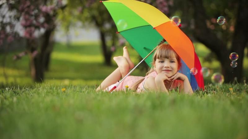 little-girl-lying-on-grass-with-umbrella_4k5cbmnnl__D.mp4