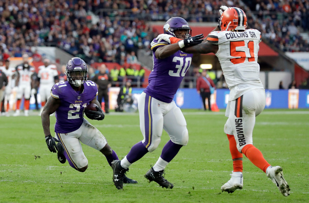. Minnesota Vikings running back Jerick McKinnon, left, scores on a 1-yard touchdown run as Vikings fullback C.J. Ham (30) holds back Cleveland Browns linebacker Jamie Collins Sr. (51) during the second half of an NFL football game against Cleveland Browns at Twickenham Stadium in London, Sunday Oct. 29, 2017. (AP Photo/Matt Dunham)