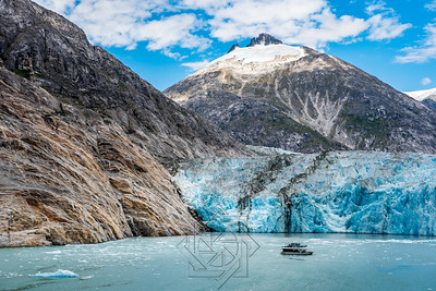 Wide angle view of Alaskan glacier with small tourist boat