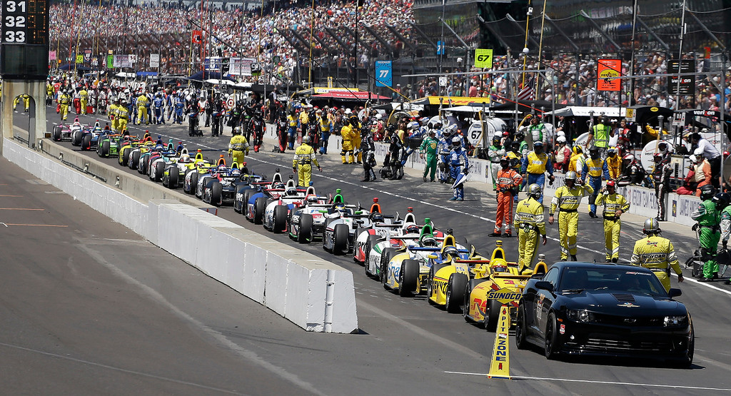 . Drivers wait in their cars along pit lane as they wait for the 98th running of the Indianapolis 500 IndyCar auto race at the Indianapolis Motor Speedway to resume during a red flag in Indianapolis, Sunday, May 25, 2014. (AP Photo/Darron Cummings)
