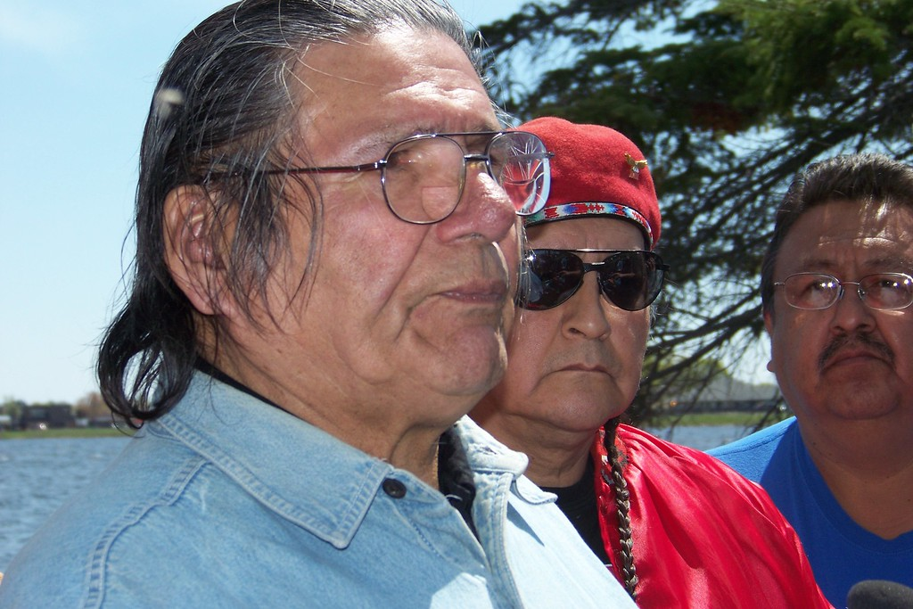 . FILE - In this May 14, 2010, file photo, American Indian activist Dennis Banks, left, speaks to reporters on Lake Bemidji, during an American Indian treaty rights protest in Bemidji, Minn. The family of Banks says he died Sunday, Oct. 29, 2017, at the age of 80. Banks was a co-founder of the American Indian Movement and a leader of the Wounded Knee occupation in 1973. (AP Photo/Jeff Baenen, File)