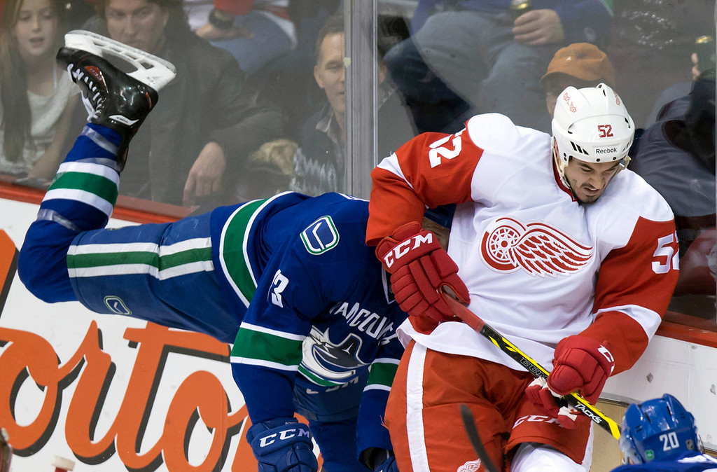 . Detroit Red Wings\' Jonathan Ericsson, right, of Sweden, and Vancouver Canucks\' Nick Bonino collide during the second period of an NHL hockey game in Vancouver, British Columbia on Saturday, Jan. 3, 2015. (AP Photo/The Canadian Press, Darryl Dyck)