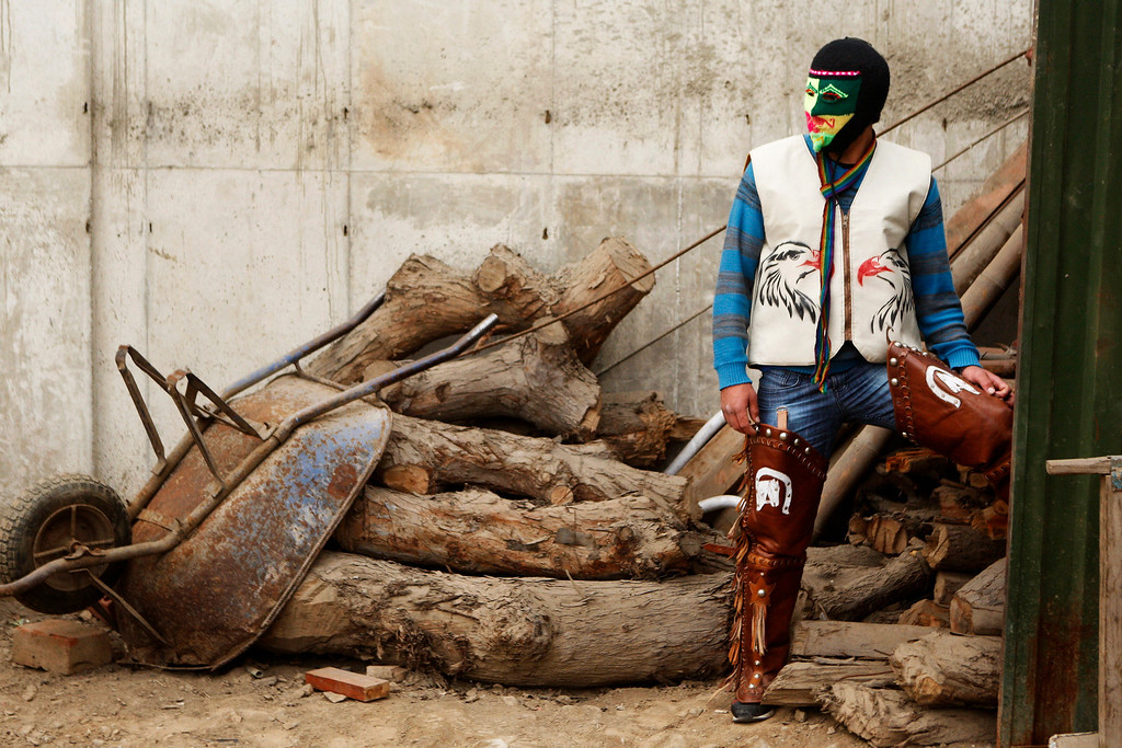". Masked fighter Alejandro Alvaro wears his costume before taking part in an Andean fight known as Takanakuy in Lima, Peru. Takanakuy, which means ""When the blood is boiling\"" in Quechua, is a ritual of unclear providence that predates Spanish colonial rule and happens twice a year, in July and just after Christmas, to settle scores. (AP Photo/Karel Navarro)"