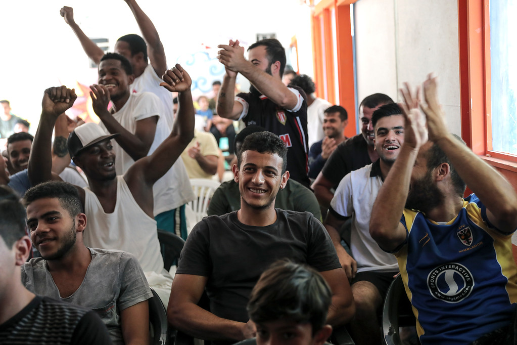 . Migrants supporting the French national soccer team celebrate a goal as they watch on a TV set the final soccer match between Croatia and France during the 2018 soccer World Cup in Russia, at Ritsona camp, northeast of Athens, Sunday, July 15, 2018. (AP Photo/Yorgos Karahalis)