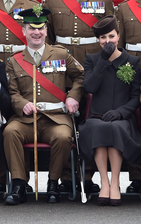 . Britain\'s Catherine, Duchess of Cambridge (R) shares a joke with an officer as they pose for a photograph with other officers during a visit of the Irish Guards during a St Patrick\'s Day parade in Mons Barracks in Aldershot, west of London, on March 17, 2015. Prince William attended the parade as Colonel of the Regiment and Britain\'s Catherine presented the traditional sprigs of shamrocks to the officers and guardsmen of the regiment. AFP PHOTO / POOL / EDDIE  MULHOLLAND/AFP/Getty Images
