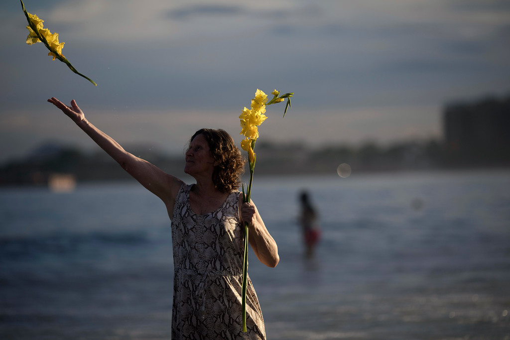 . A woman offers flowers to Yemanja, goddess of the sea, for good luck in the coming year during New Year\'s Eve festivities in Rio de Janeiro, Brazil, Sunday, Dec. 31, 2017. The belief in the goddess comes from the African Yoruba religion brought to America by West African slaves. (AP Photo/Leo Correa)