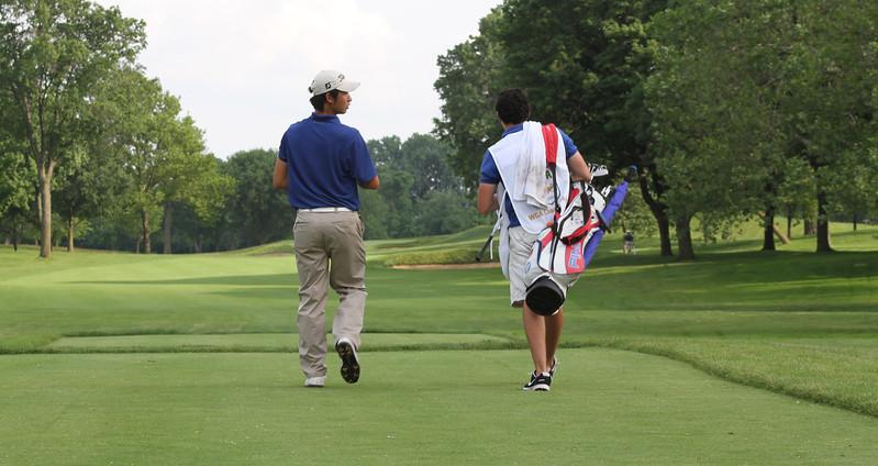 James Yoon,Bradenton, Fla., walks down the fairway with his caddie.