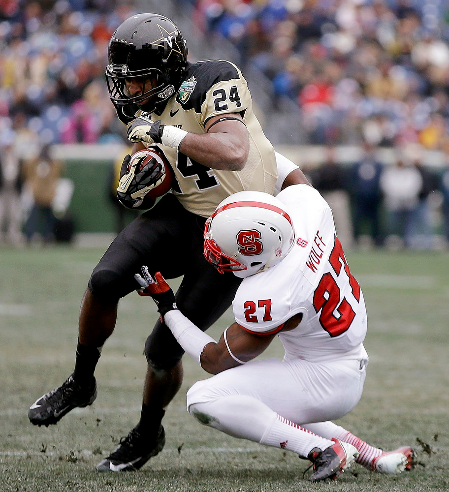 . Vanderbilt wide receiver Wesley Tate (24) is stopped by North Carolina State safety Earl Wolff (27) in the first quarter of the Music City Bowl NCAA college football game, Monday, Dec. 31, 2012, in Nashville, Tenn. (AP Photo/Mark Humphrey)