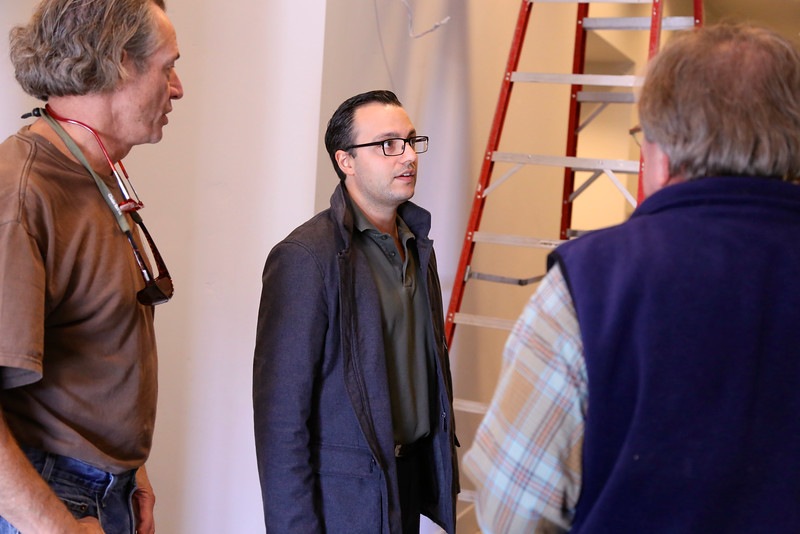 Ali Youssefi of CFY Development visits with artist William Ishmael (right) during his art installation at the Warehouse Artist Lofts on R Street. (Photo by Joan Cusick)