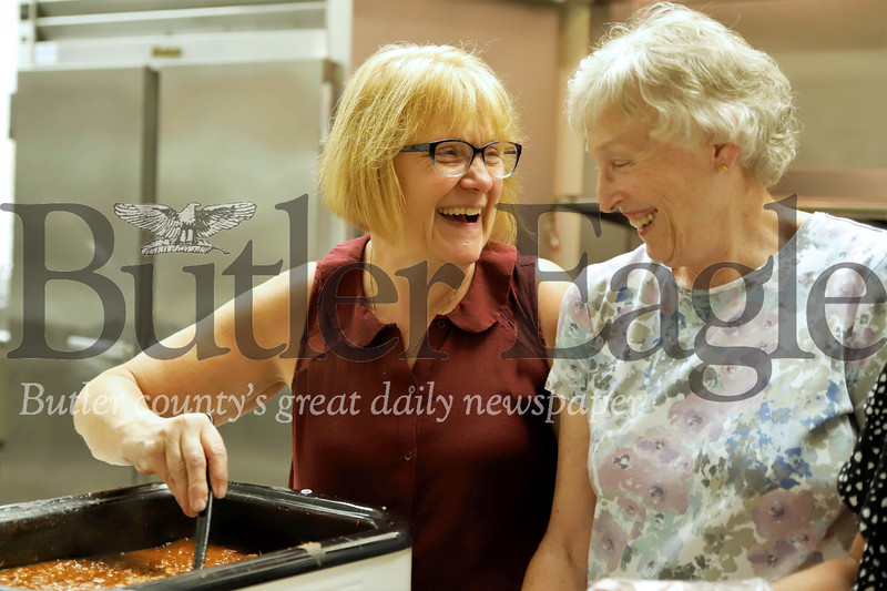 Katie's Kitchen director Loretta Bachman (left) shares a laugh with longtime volunteer Raylene Jindra serving chilli at Thursday night's community dinner at St. Mark's Evangelical Church . Seb Foltz/Butler Eagle