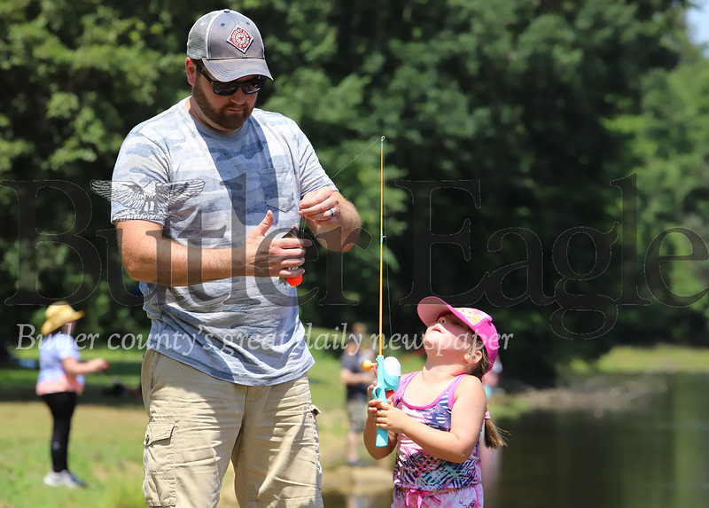 Justin Ross of Butler takes a fish off the line of his daughter Brooklyn's, 4, fishing pole at Concordia's Kids Fishing Days Saturday at Saxony Farm Estates. Seb Foltz/Butler Eagle 07/25/20