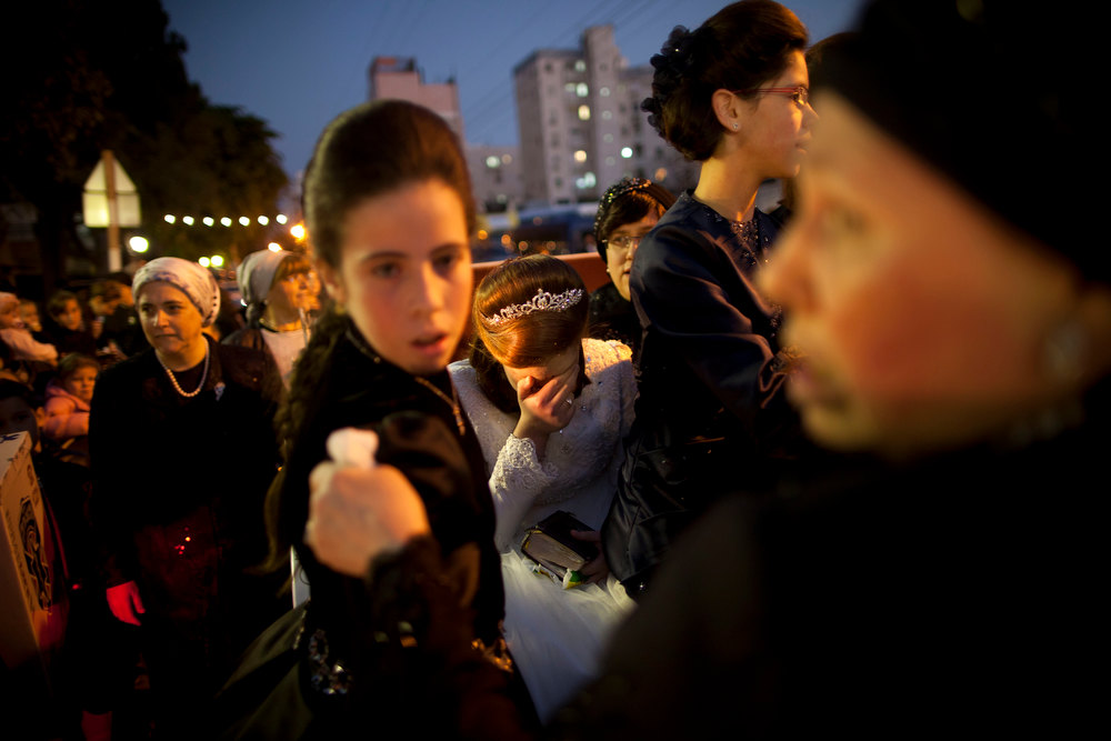 Description of . An Ultra-Orthodox Jewish bride, center, arrives for her wedding ceremony in Netanya, Israel, Wednesday, Jan. 2, 2013. Thousands of people attended the wedding. (AP Photo/Oded Balilty)