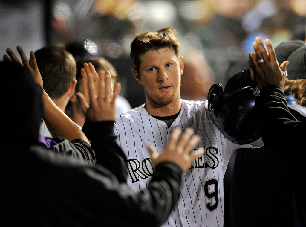 . Colorado Rockies\' DJ LeMahieu is congratulated by his teammates after scoring on a single by Charlie Blackmon in the fifth inning of a baseball game against the San Diego Padres on Friday, Sept. 5, 2014, in Denver. (AP Photo/Chris Schneider)