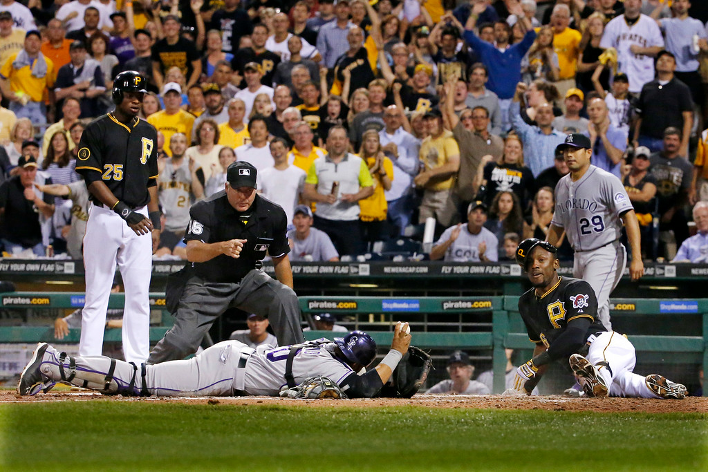 . Colorado Rockies catcher Wilin Rosario shows the ball to umpire Tim Timmons as he makes the out call on Pittsburgh Pirates\' Starling Marte, right, who attempted to stretch a run scoring triple into an inside the park home during the sixth inning of a baseball game in Pittsburgh Friday, July 18, 2014. At left is Pirates\' Gregory Polanco (25) who scored on the play, and right rear is Colorado Rockies starting pitcher Jorge De La Rosa (29). (AP Photo/Gene J. Puskar)