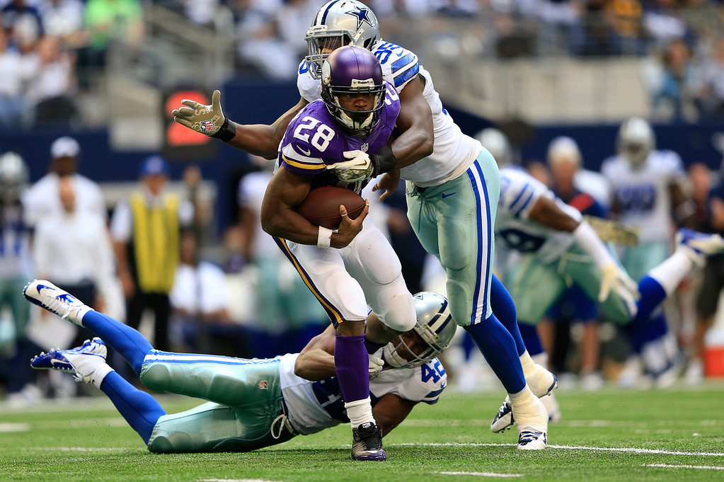 . Running back Adrian Peterson #28 of the Minnesota Vikings carries the ball during the game against the Dallas Cowboys at Cowboys Stadium on November 3, 2013 in Arlington, Texas.  (Photo by Jamie Squire/Getty Images)