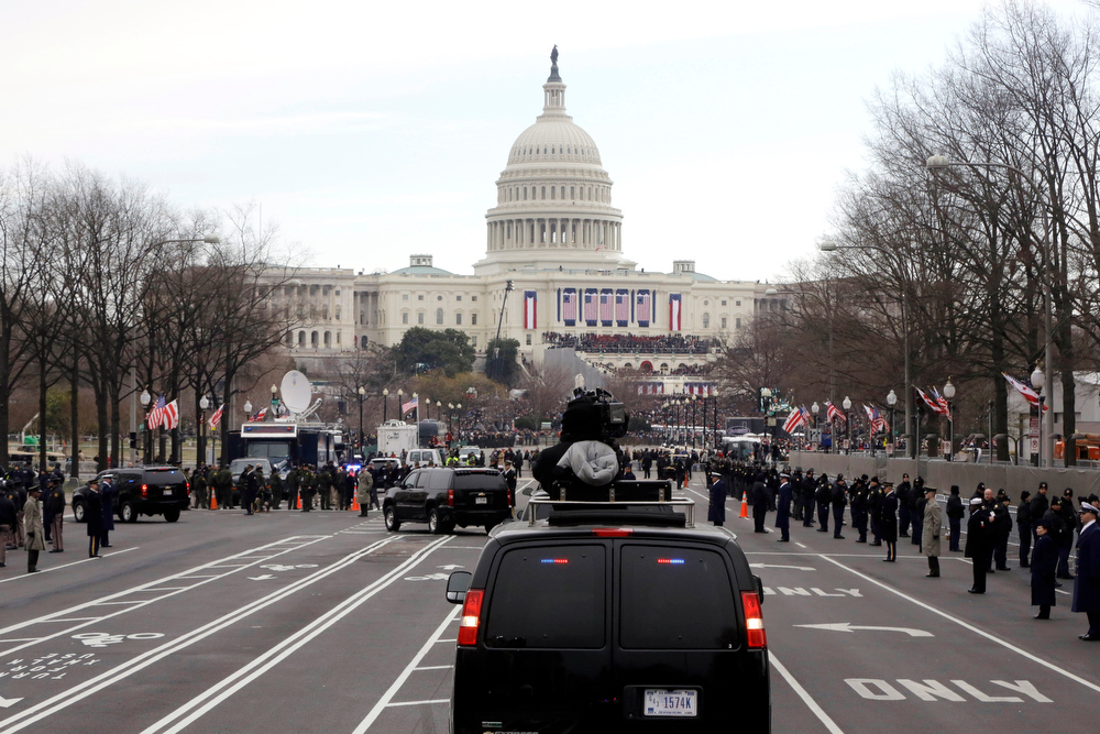 Description of . President Barack Obama and first lady Michelle Obama ride up Pennsylvania Avenue in the presidential motorcade towards the U.S. Capitol in Washington, Monday, Jan. 21, 2013, ahead of his ceremonial swearing in during the 57th Presidential Inauguration. (AP Photo/Charles Dharapak)