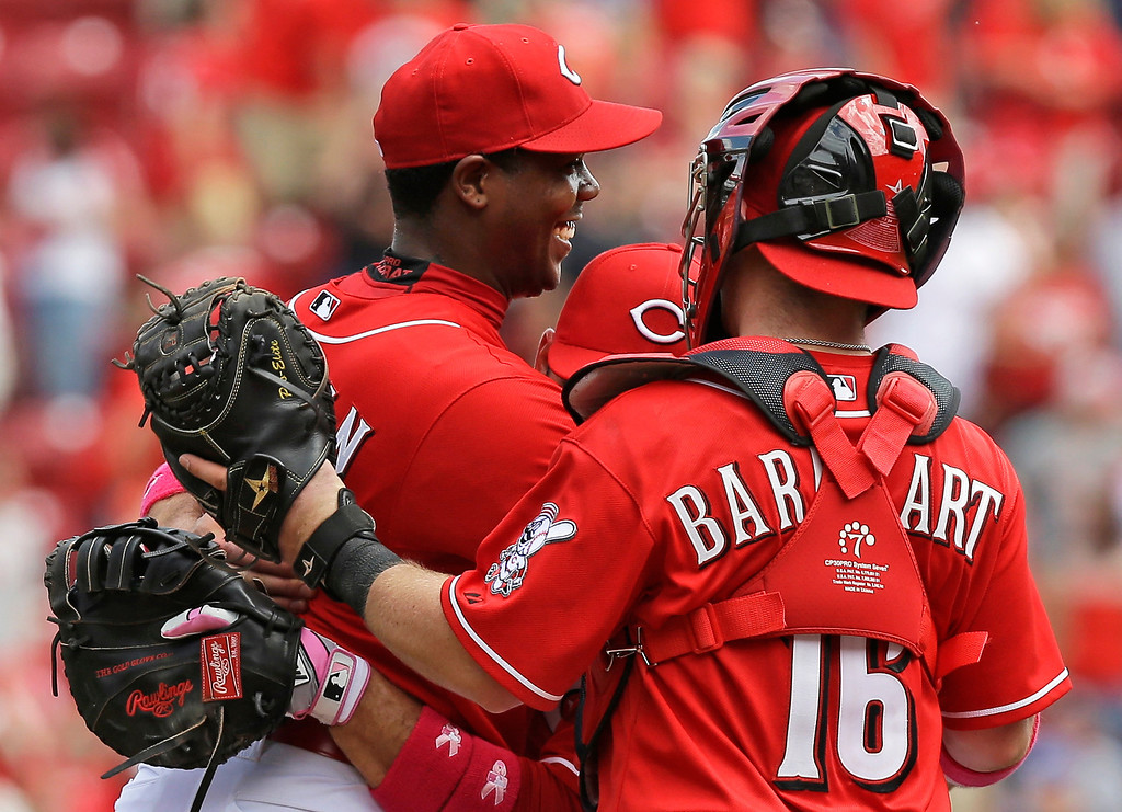 . Cincinnati Reds relief pitcher Aroldis Chapman, left, is hugged by Joey Votto and Tucker Barnhart (16) after Chapman earned his first save of the season in the Reds 4-1 win over the Colorado Rockies in a baseball game, Sunday, May 11, 2014, in Cincinnati. Chapman was making his first appearance since being hit in the head with a line drive in spring training. (AP Photo/Al Behrman)