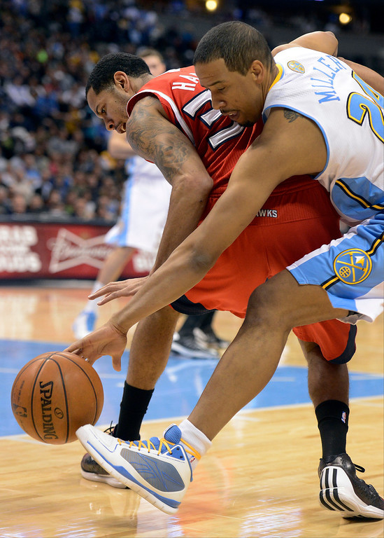. Devin Harris (34) of the Atlanta Hawks knocks the ball away from Andre Miller (24) of the Denver Nuggets to force a turn over March 4,  2013 at Pepsi Center. (Photo By John Leyba/The Denver Post)