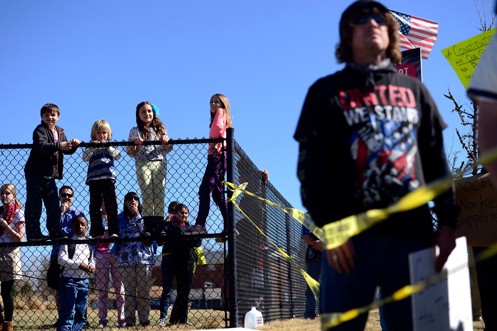 . DENVER, CO - APRIL 3: From left to right, Wade Jahnke, 7, Sam Pozzetta, 6, Avarie Jahnke, 9, and Sophia Pozzetta, 10, stand on the fence of Bill Roberts School to get a better view as Barack Obama\'s motorcade leaves after a speech at the Denver Police Academy. Both sides gathered outside of the complex to share their respective views. (Photo by AAron Ontiveroz/The Denver Post)